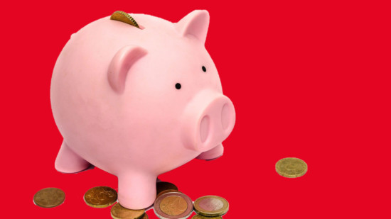 Sparschwein mit herumliegenden Münzen